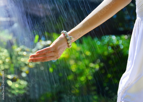 Female's hand under the raindrops