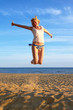 happy smiling girl jumping on beach against blue sky