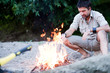 man standing by the fire on the river beach -series - 43010616