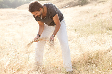 man on dry meadow picking grass straws to start a fire -series