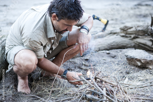 man making a fire on the beach by the river - series