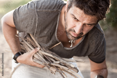 rough man picking wood to make fire by the river - series