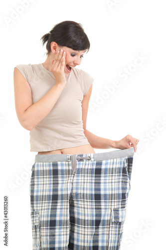 surprised weight lost woman in tbig pants