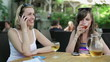 Two happy female friends talking on cellphone and drinking wine