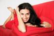 Frau auf rotem Sofa