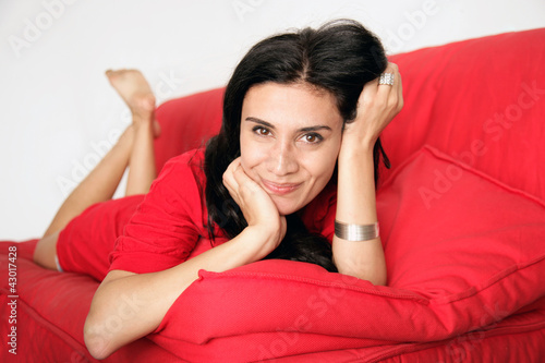 Frau liegt auf rotem Sofa