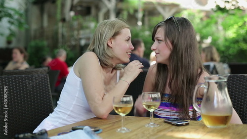 Woman talking secret to her friend in outdoor bar