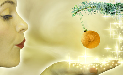 Christmas concept with woman blowing to bauble