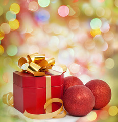Christmas red gift and baubles on colorful background