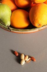Frutero con naranjas, peras y cacahuetes