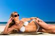 Attraktive Frau im Bikini sitzt in Sonne am Strand