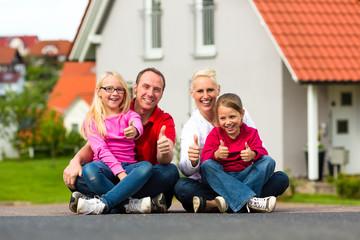 Familie sitzt vor ihrem Haus
