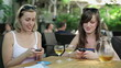Female friends sending text message in outdoor bar