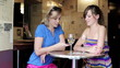 Female friends with smartphone in bar