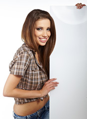 Happy smiling beautiful young  woman showing blank signboard, is