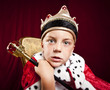 little boy dressed ad a king on red velvet background