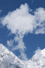 Picturesque cloud over snow tops.