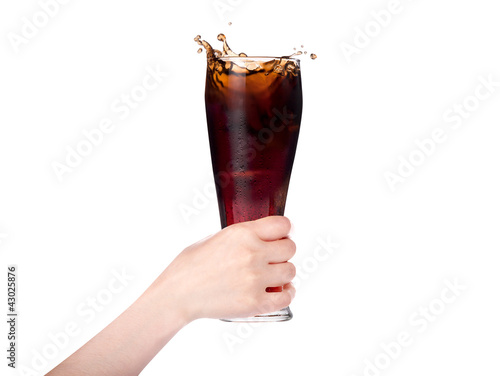 Woman hand holding fresh Cola with ice cubes