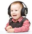 Cute little boy enjoying music using headphones