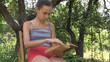 Teenage girl reading book in orchard outdoors