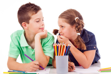 Two children draw with colorful crayons and smile, isolated over