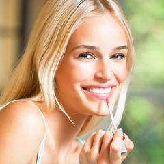 Happy beautiful woman applying lipstick