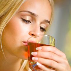 Happy woman drinking juice