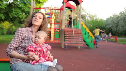 Mother and baby on children's playground