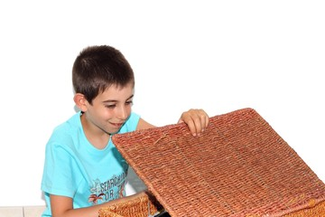 young boy opening a  wicker basket