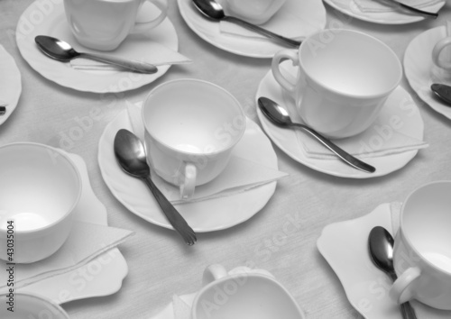 Plastic cups and saucers with spoons