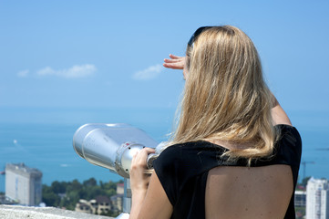 Woman on vacation looking through binoculars