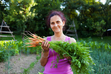 Young woman farmer holding vegetables