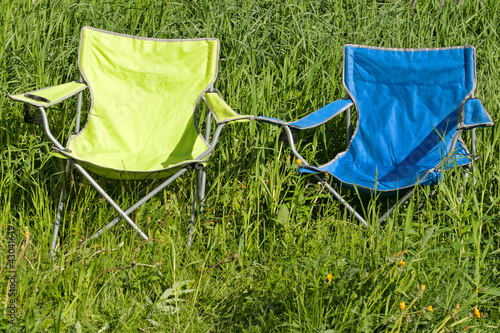 Two empty folding chair on the green grass