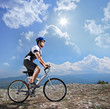 A view of a biker riding a mountain bike on a sunny day