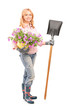 Full length portrait of a female gardener holding  flowers and a