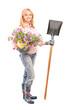 Full length portrait of a female gardener holding  flowers and a