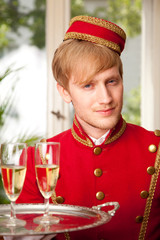 hotelpage in roter uniform serviert chamapgner