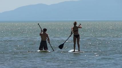 Paddle boarding couple on lake