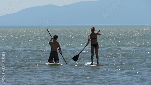 Paddle boarding couple on lake