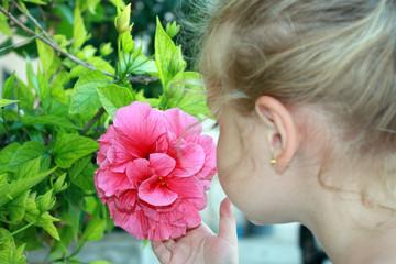 Bambina in giardino che odora un fiore