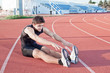 A young man makes an athlete stretching. Against the background