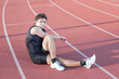 A young athlete makes stretch. Against the background the treadm