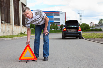 Mature man sets triangle warning sign on road  Car with blinker