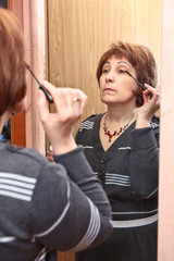 Mature Caucasian woman applying make-up against mirror