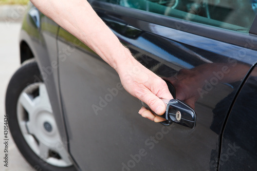 Driver`s hand opening car door of black land vehicle