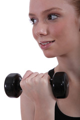 Girl lifting dumbbell, studio shot