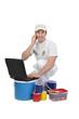 Decorator with laptop and tins of paint