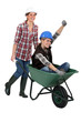 Two female construction workers with wheelbarrow