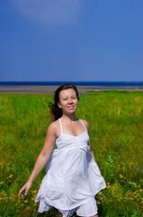 young happy girl walking in green field