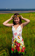 beautiful girl in wreath of flowers in meadow on sunny day